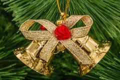 Золотой колокол рождества на елевой ветви Стоковое Изображение RF
