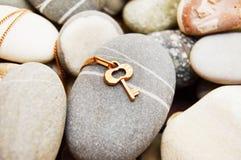 Золотой ключ на камешках моря стоковая фотография rf