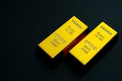 2 золотой монеты бара на черной предпосылке Стоковая Фотография