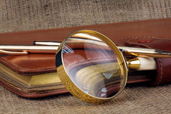 Золотой дневник дела ручки, лупа на увольнении Стоковая Фотография