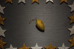 Золотой орнамент конуса сосны на шифере с рамкой звезды Стоковая Фотография RF