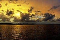Золотой пасмурный Seascape захода солнца с отражениями морской воды Стоковые Фотографии RF