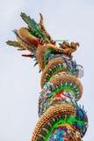 Золотой дракон обернутый вокруг красного поляка стоковое фото rf
