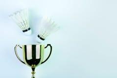 Золотой трофей и Shuttlecock на белой предпосылке с Стоковая Фотография