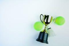 Золотой трофей, теннисный мяч Shuttlecock и на белом bac Стоковая Фотография