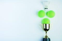 Золотой трофей, теннисный мяч Shuttlecock и на белом bac Стоковые Изображения