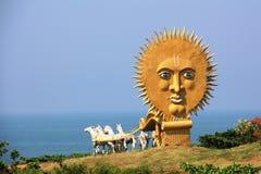 Золотой экипаж с белыми лошадями в виске сложном Murudeshwar, нося к морю с огромным солнцем Стоковая Фотография RF