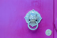 Золотой knocker двери в форме льва с кольцом на красной древесине Стоковое Изображение RF