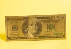 Золотой 100 u Долларовая банкнота s на желтом цвете Стоковая Фотография