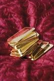 Золото в слитках на красном бархате стоковое изображение