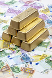 Золото в слитках на куче примечаний евро Стоковые Фото
