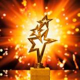 Золото играет главные роли трофей против предпосылки искр стоковое изображение