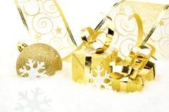 Золотые безделушки рождества, подарки, снежинки с золотой лентой на снеге Стоковые Фото