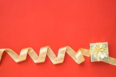Золотые лента и подарочная коробка на красной предпосылке Стоковое Изображение RF