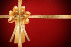 Золотые лента и смычок, обруч на красной кожаной предпосылке подарочной коробки текстуры Стоковая Фотография RF