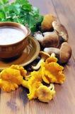Золотые лисички и суп гриба плюшки пенни с чашкой и spo Стоковая Фотография