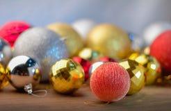Золотые и красные и серебряные шарики рождества на деревянном столе Стоковая Фотография