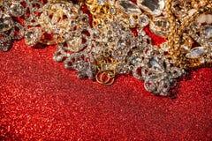 Золотые и серебряные ювелирные изделия на красной сияющей предпосылке яркого блеска Стоковое Изображение