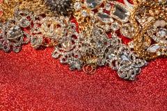 Золотые и серебряные ювелирные изделия на красной сияющей предпосылке яркого блеска Стоковая Фотография