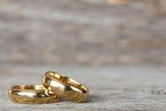 Золотые кольца на деревянной поверхности Стоковые Изображения RF