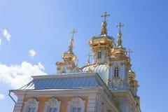 Золотые куполы и украшение дворца Peterhof грандиозного против яркого неба Стоковые Фотографии RF