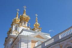 Золотые куполы и украшение дворца Peterhof грандиозного против яркого неба Стоковое Изображение RF