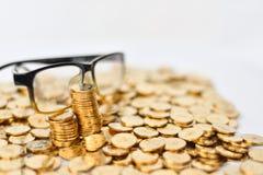 Золотые монетки и glassess Стоковые Изображения