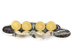 Золотые монетки стоя на серебряных монетах стоковые изображения