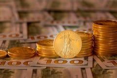 Золотые монетки штабелированные на новых долларовых банкнотах дизайна 100 Стоковые Изображения RF