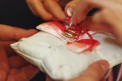 Золотые обручальные кольца лежат на белой подушке с красной лентой Стоковая Фотография