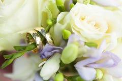 Золотые обручальные кольца на букете свадьбы белых роз и цветков фиолета Стоковое Изображение