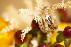 Золотые обручальные кольца на букете свадьбы желтых цветков Стоковая Фотография RF