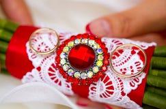 Золотые обручальные кольца на букете свадьбы с красными лентой и фибулой Стоковое Изображение