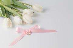 Золотые обручальные кольца над розовой лентой Стоковая Фотография