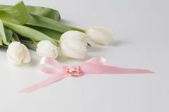 Золотые обручальные кольца над розовой лентой Стоковое Фото