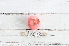 Золотые обручальные кольца на розовом символе macaron и влюбленности с сердцами Стоковые Изображения RF