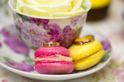Золотые обручальные кольца на розовых и желтых macaroons Стоковые Фото
