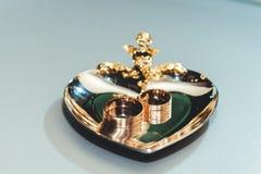 Золотые обручальные кольца на сердце золотой посуды Стоковое Изображение