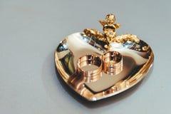 Золотые обручальные кольца на сердце золотой посуды Стоковое Изображение RF