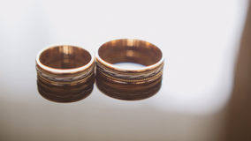 Золотые обручальные кольца на таблице стекел зеркала - одно лежит около других Стоковые Фотографии RF