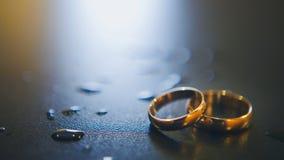 Золотые обручальные кольца на таблице с падениями воды Стоковая Фотография