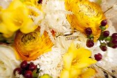 Золотые обручальные кольца с диамантами на букете свадьбы желтых цветков Стоковое фото RF