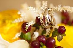 Золотые обручальные кольца с диамантами на букете свадьбы желтых цветков Стоковая Фотография