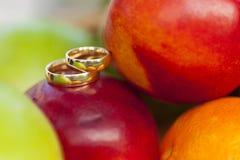 Золотые обручальные кольца smoth среди красочных плодоовощей Стоковые Изображения