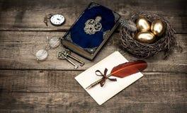 Золотые пасхальные яйца и античная книга библии Стоковое фото RF