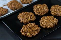 Золотые печенья овсяной каши с яблоком и гайки на черной плите Стоковое фото RF