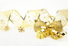 Золотые подарки рождества, безделушки с золотой лентой на снеге Стоковые Изображения RF