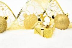 Золотые подарки рождества, лента безделушки на снеге Стоковая Фотография