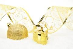 Золотые подарки рождества, лента безделушки на снеге Стоковые Фотографии RF
