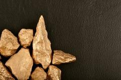 Золотые самородки на черной коже предпосылки. Крупный план. Стоковая Фотография RF